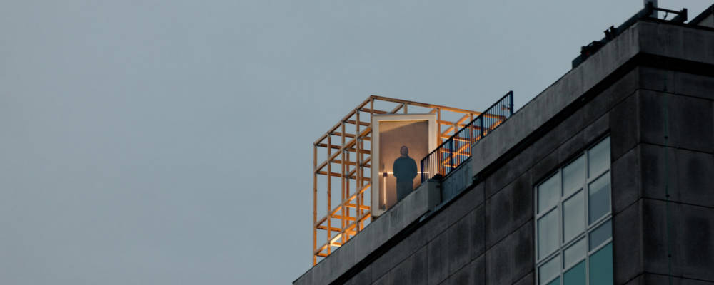 Freedom Festival, The Vigil Joanne Leighton, WLDN, Global Streets 2021. A man peers out over the city of Hull from The Vigil, a structure with a large window that sits atop a tall city building.