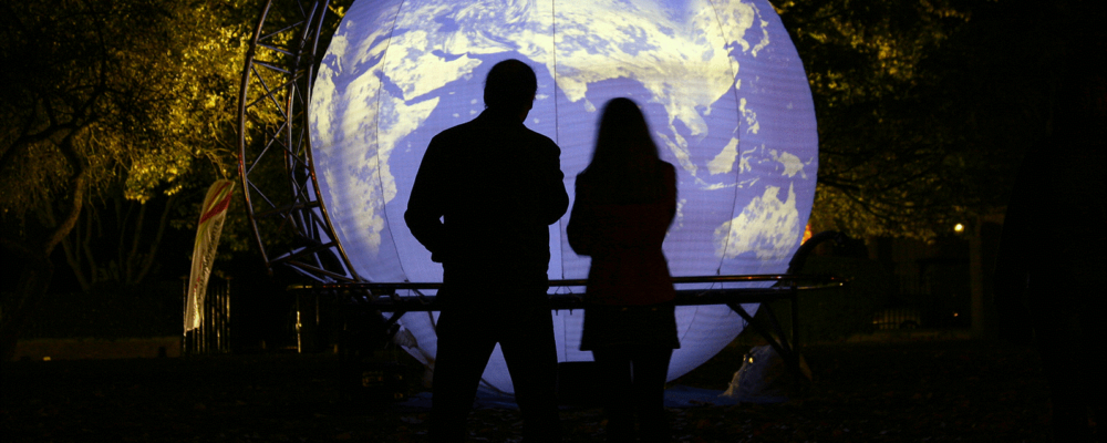Lightweight, Impossible Arts, Autumn Glow, 2021. Two audience members are silhouetted by the light coming from giant glowing globe.