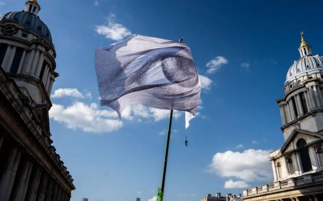 DanAcher, WeAreWatching Greenwich, GDIF 2021. A flag with a giant eye printed flies against a blue sky.