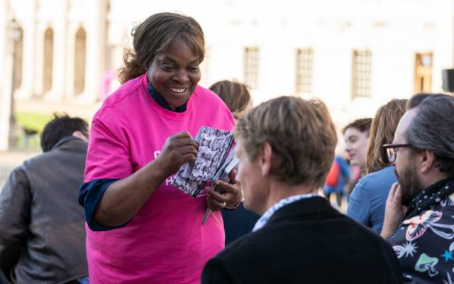 DanAcher, WeAreWatching Ceremony Greenwich, GDIF 2021. A black woman in a GDIF volunteer T-shirt hands out a programme at the opening ceremony for GDIF 2021.
