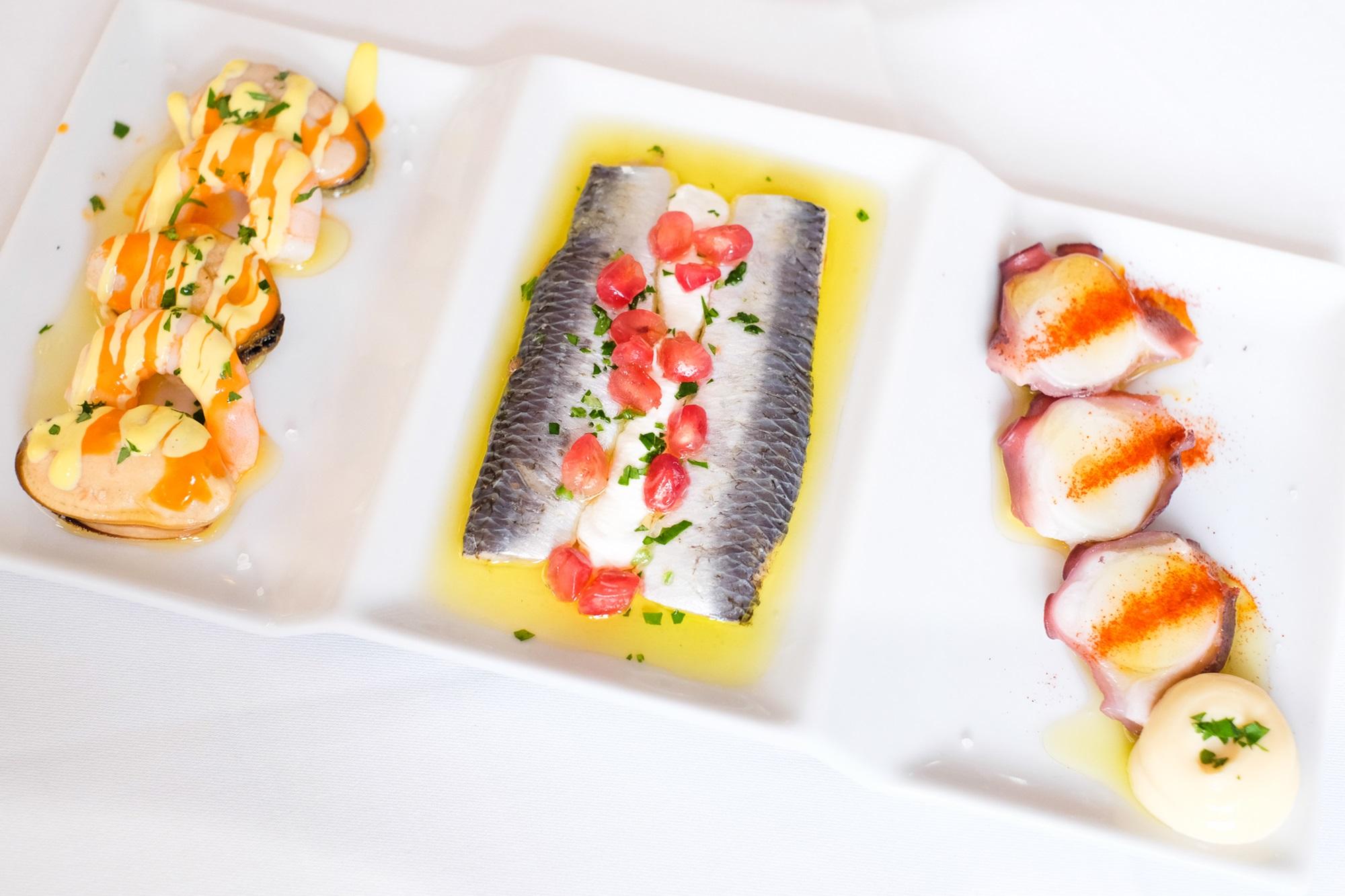 Mejillones y gambas, sardinas y pulpo. Trío de tapas de pescado y marisco.