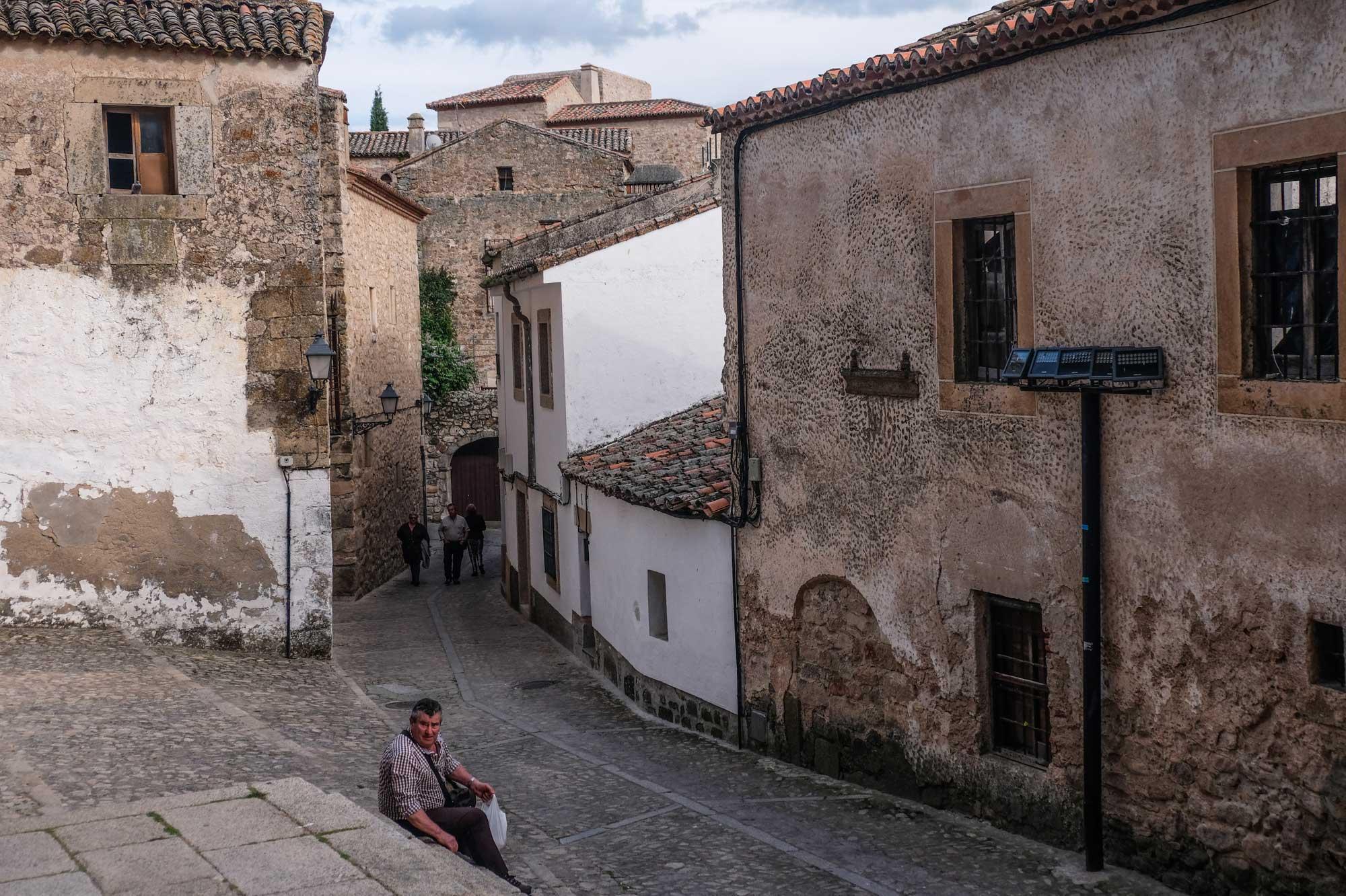 Calle empedrada de la zona amurallada de Trujillo con señor sentado.