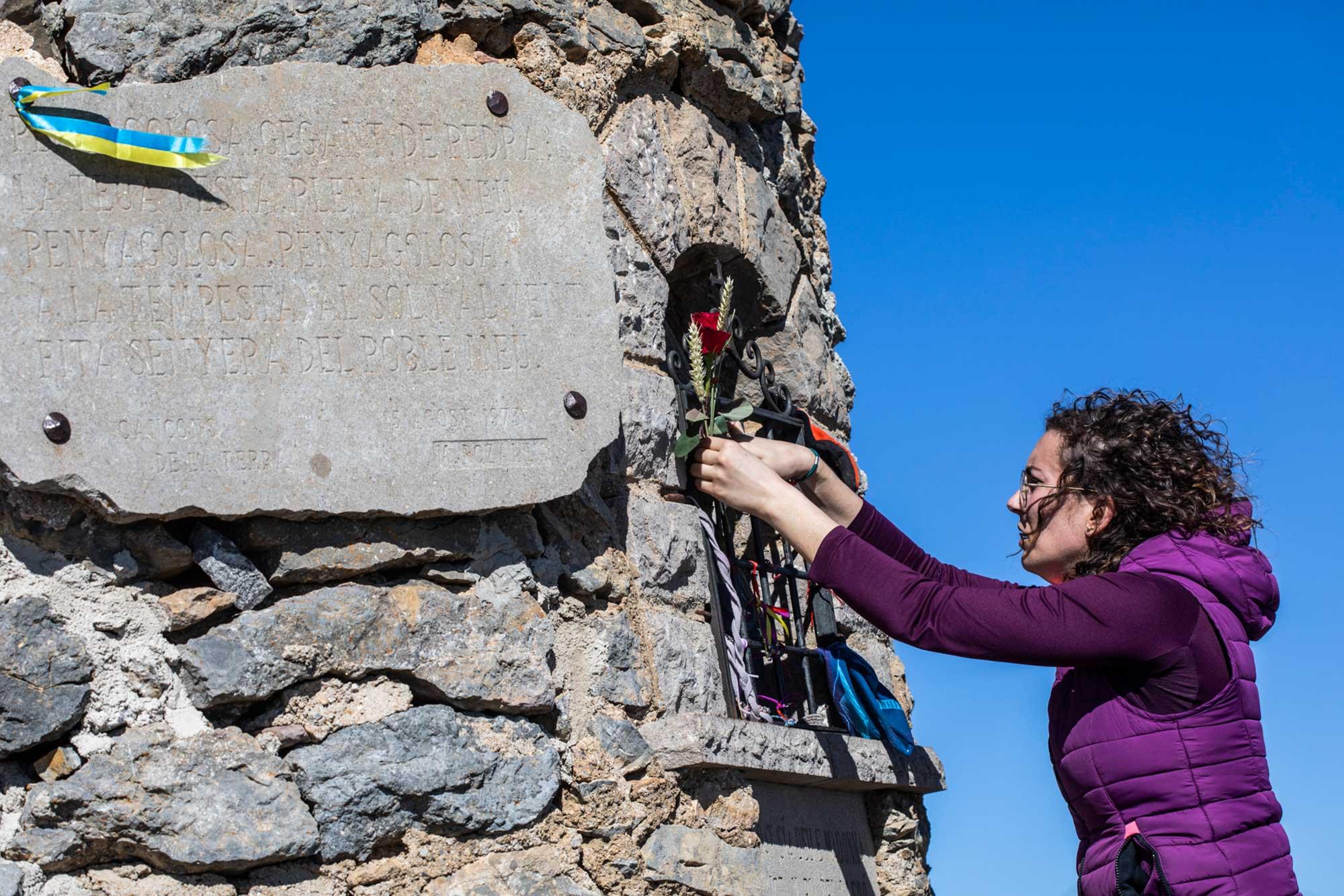 En la cima, una montañera hace una ofrenda al Gigante de Piedra.