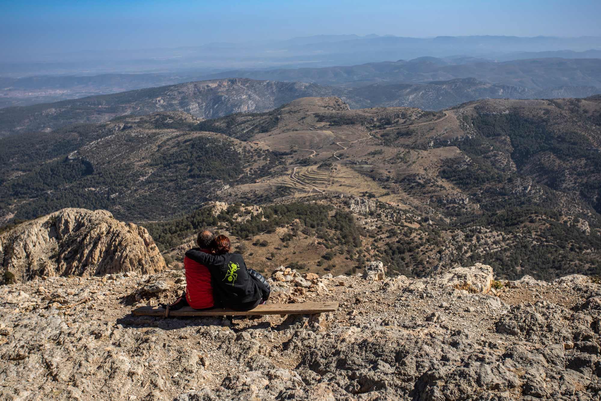 Una pareja sentada en la cima del Penyagolosa.