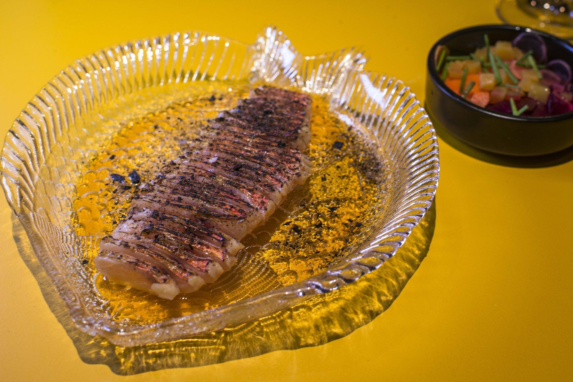 El salmonete con encurtidos se calienta en el mismo plato con un soplete.