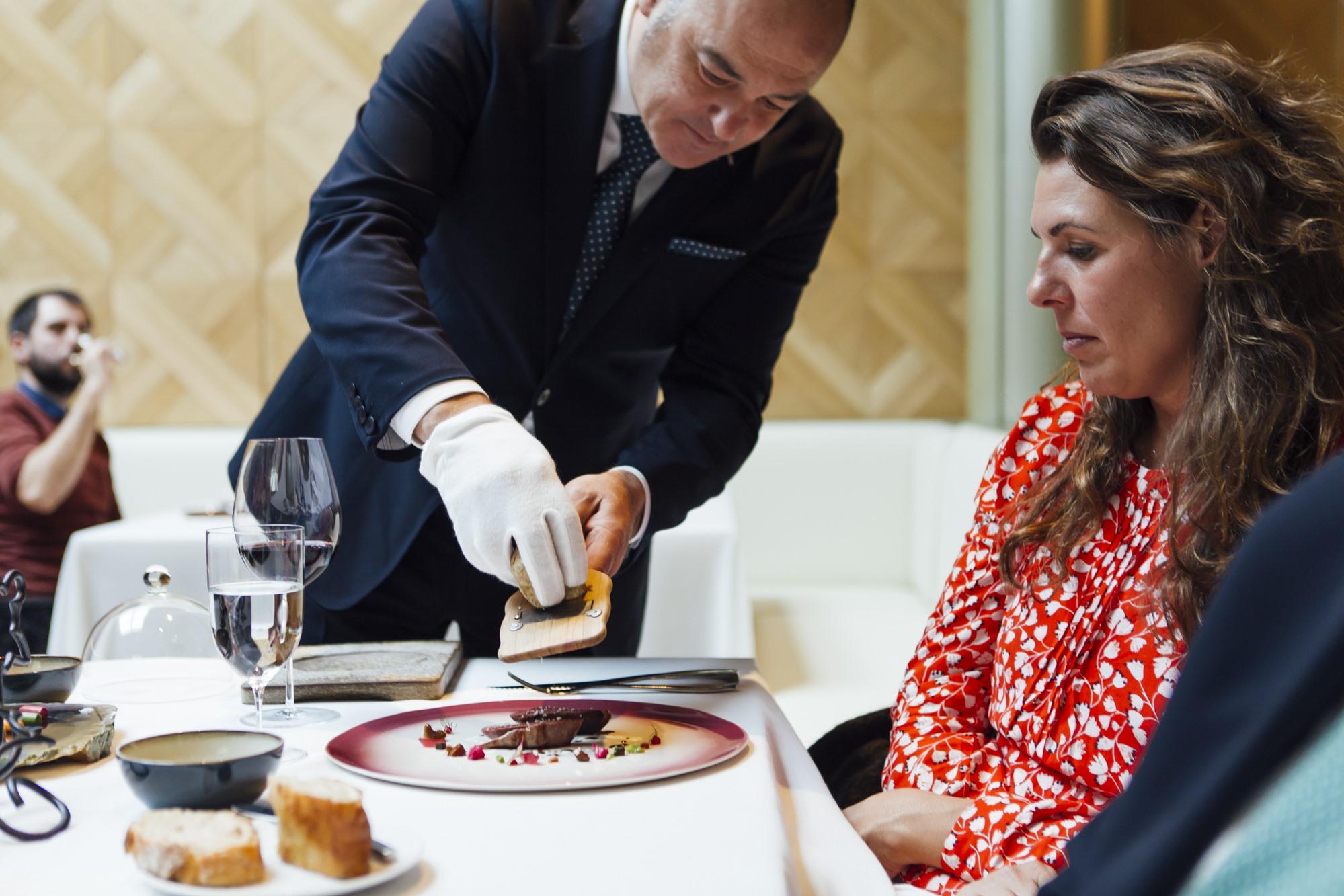 El jefe de sala, Juan Carlos Ibáñez, ralla trufa blanca sobre el pichón al carbón con matices vegetales, salsa especiada y grano 'bianco perla'.