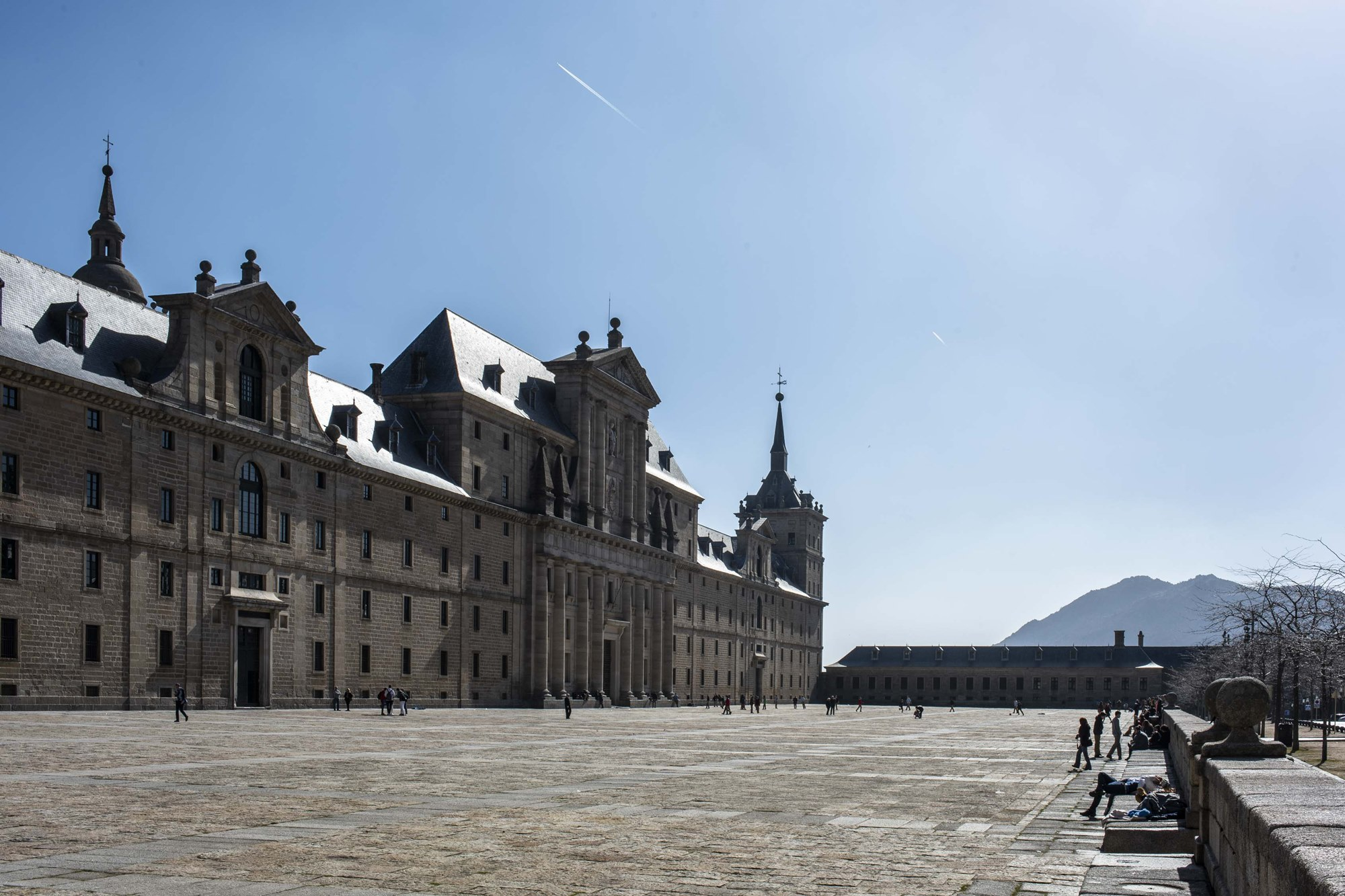 Varios turistas toman el sol en la gran explanada que rodea el monumento.