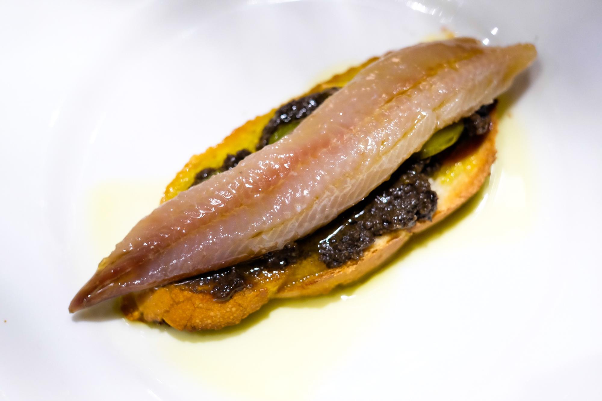 Sardina ahumada con barbacoa, aceituna negra y pepinillos.