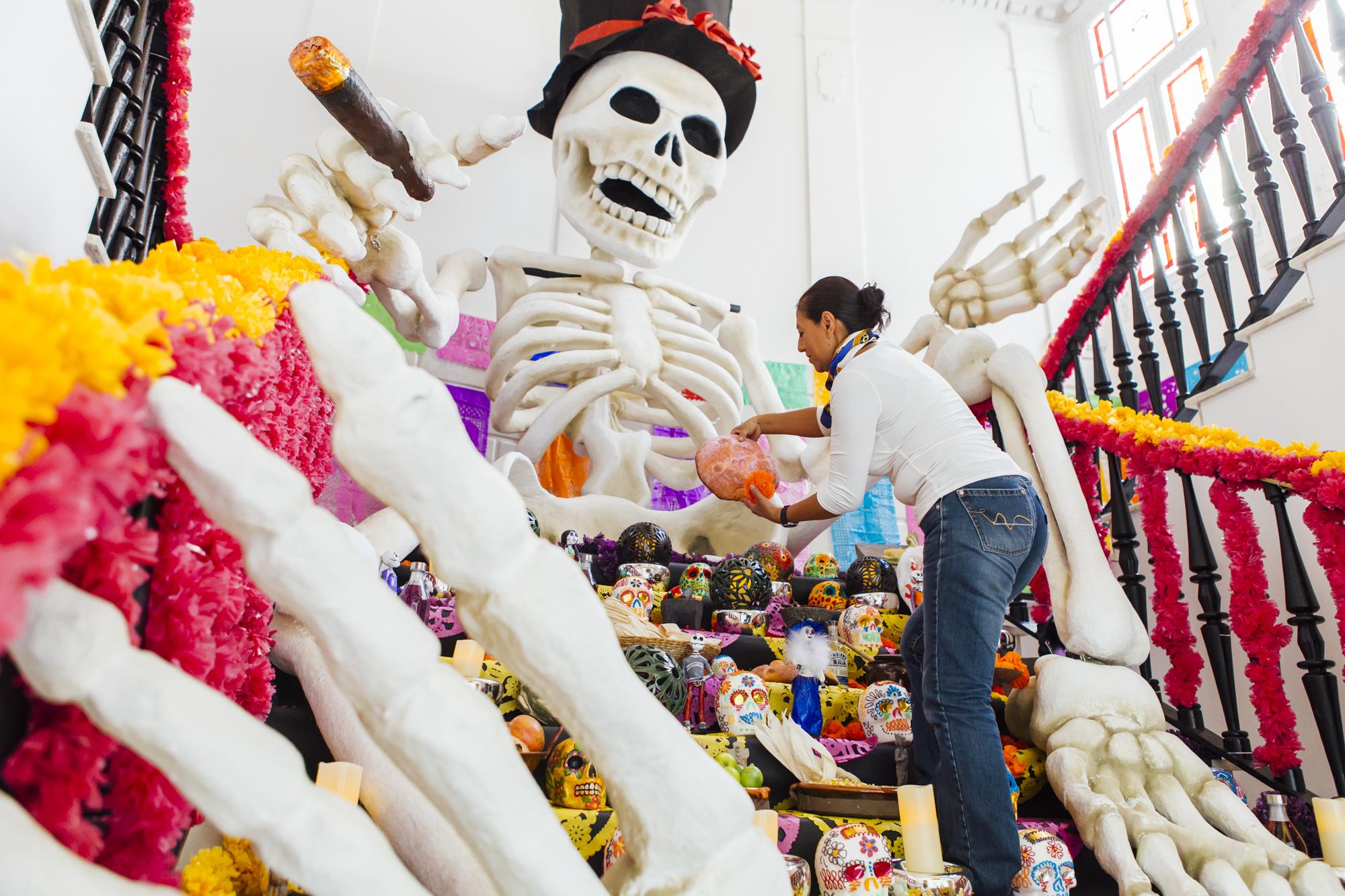 Carmen Rosas, encargada de los talleres de artesanía, completando la ofrenda a los difuntos con pan de muertos, cuyo aroma flota en el 'hall'.