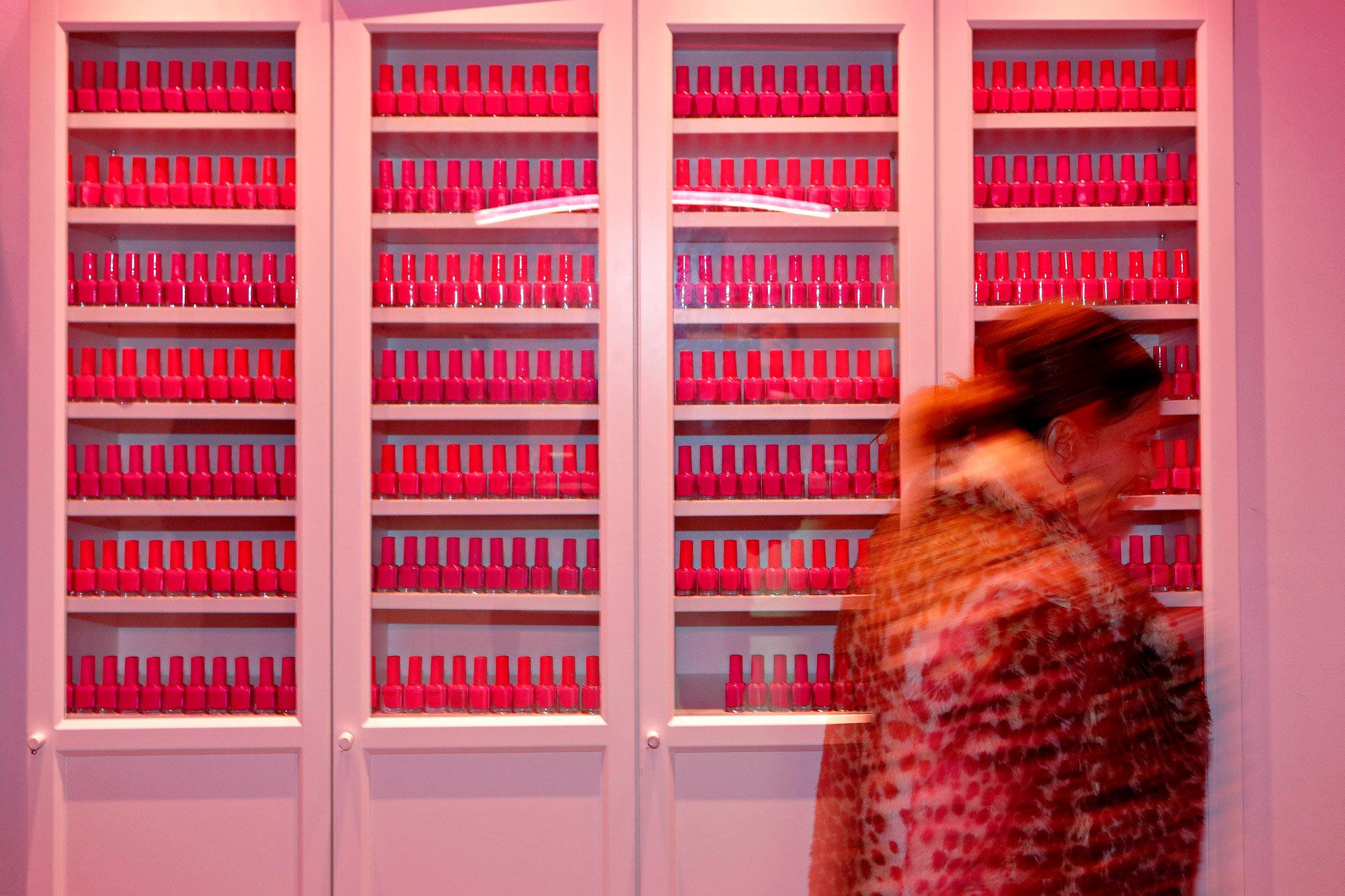 El vestíbulo está repleto de botes de esmalte de uñas bañados en una luz rosa, para deleite de los clientes.
