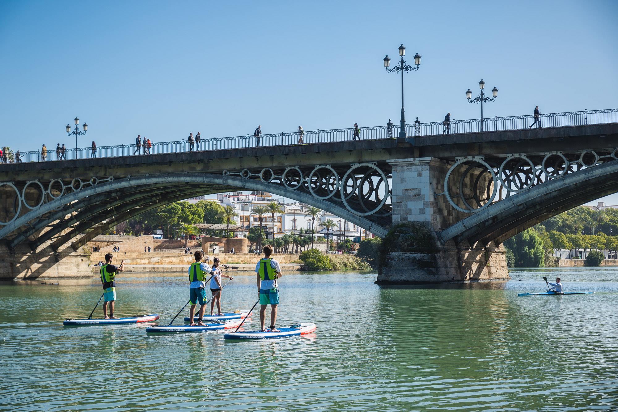 Transeúntes pasean por el icónico Puente de Triana mientras otros pasan por debajo navegando.