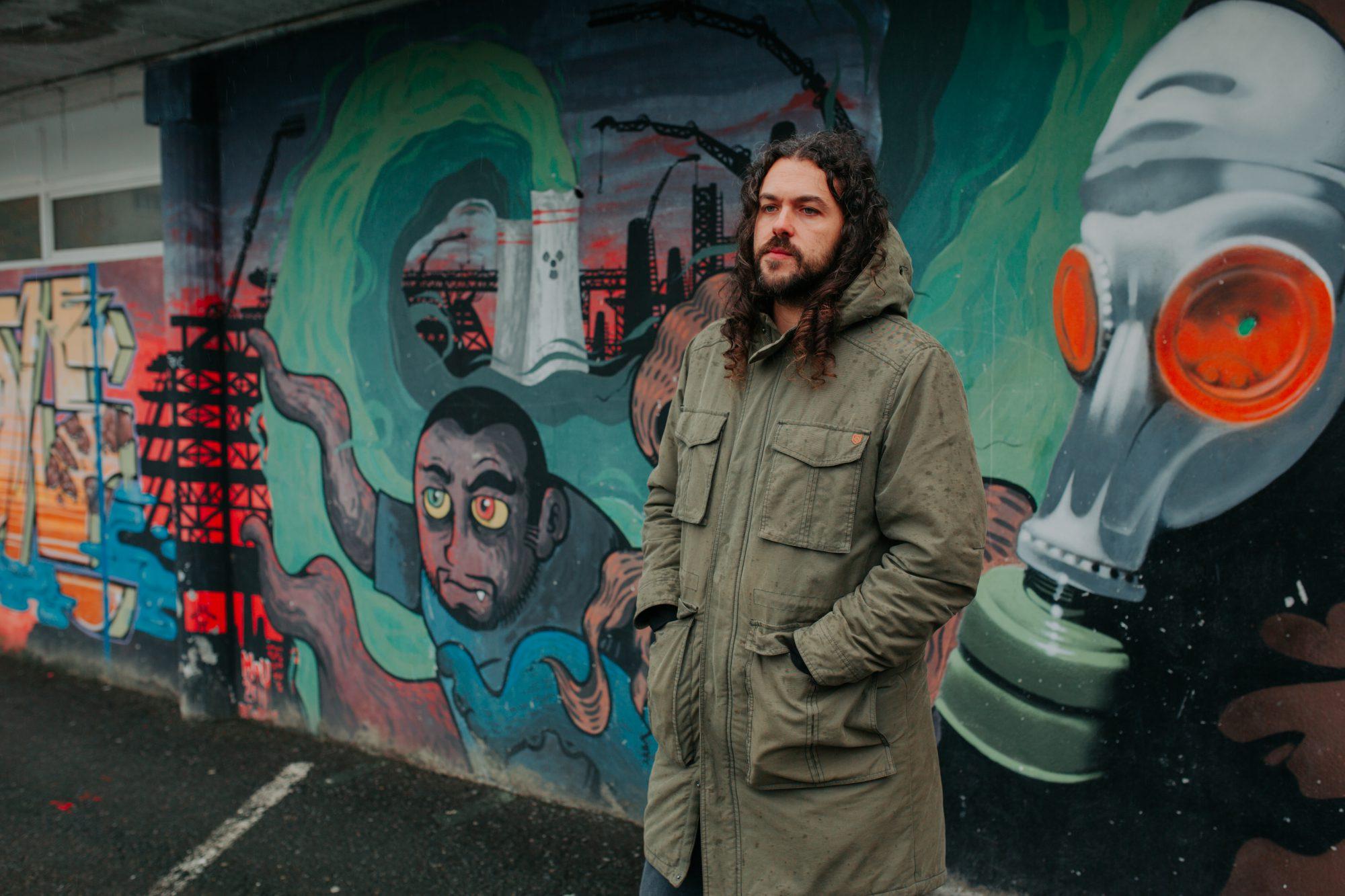 Street art en Ordes: Mou Mutante delante de una de sus obras realizada junto al grafitero X Pen.