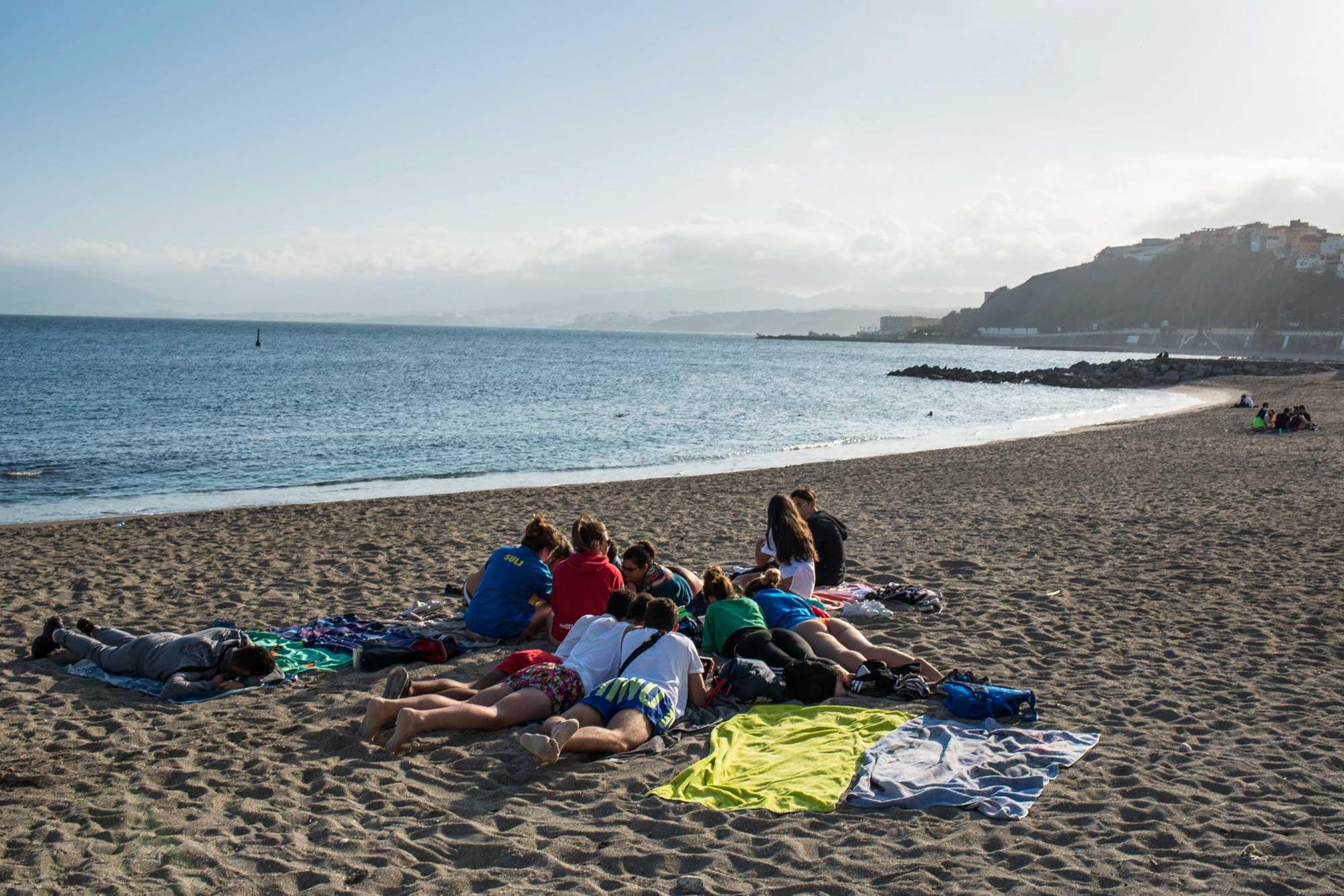 Grupo de jóvenes tumbados en la Playa de la Ribera.