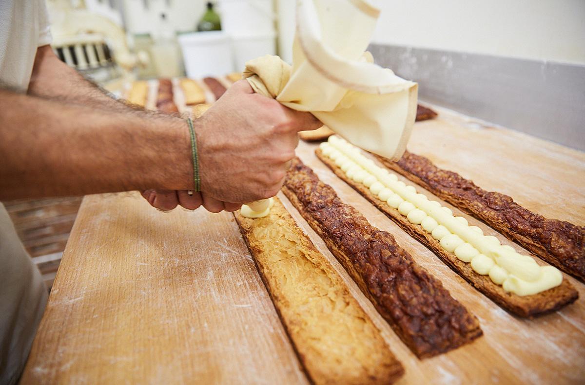 Rellenando de crema pastelera las famosas cocas de crema de la casa.