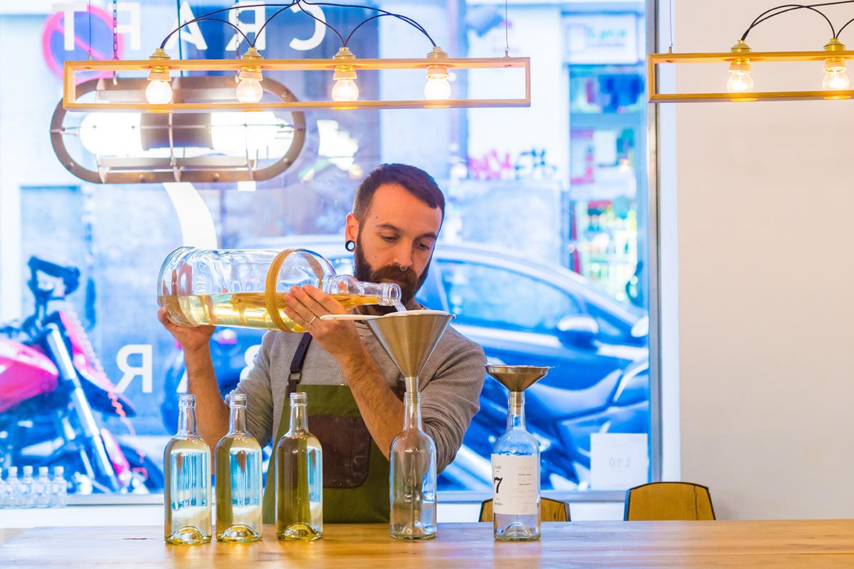Narciso Bermejo embotellando los destilados artesanales que se sirven en el alojamiento.