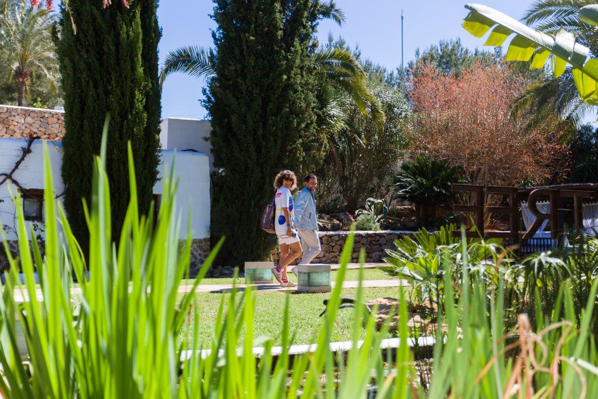 Una pareja pasea entre las fuentes y las flores de la finca.