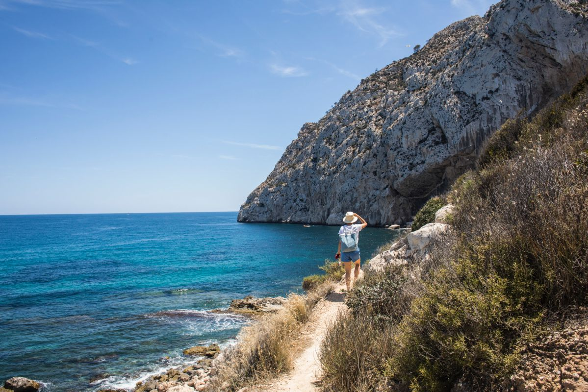 Una turista camina con su perro por el sendero que lleva hacia la cala del Peñón de Ifach, en Calpe, Alicante.