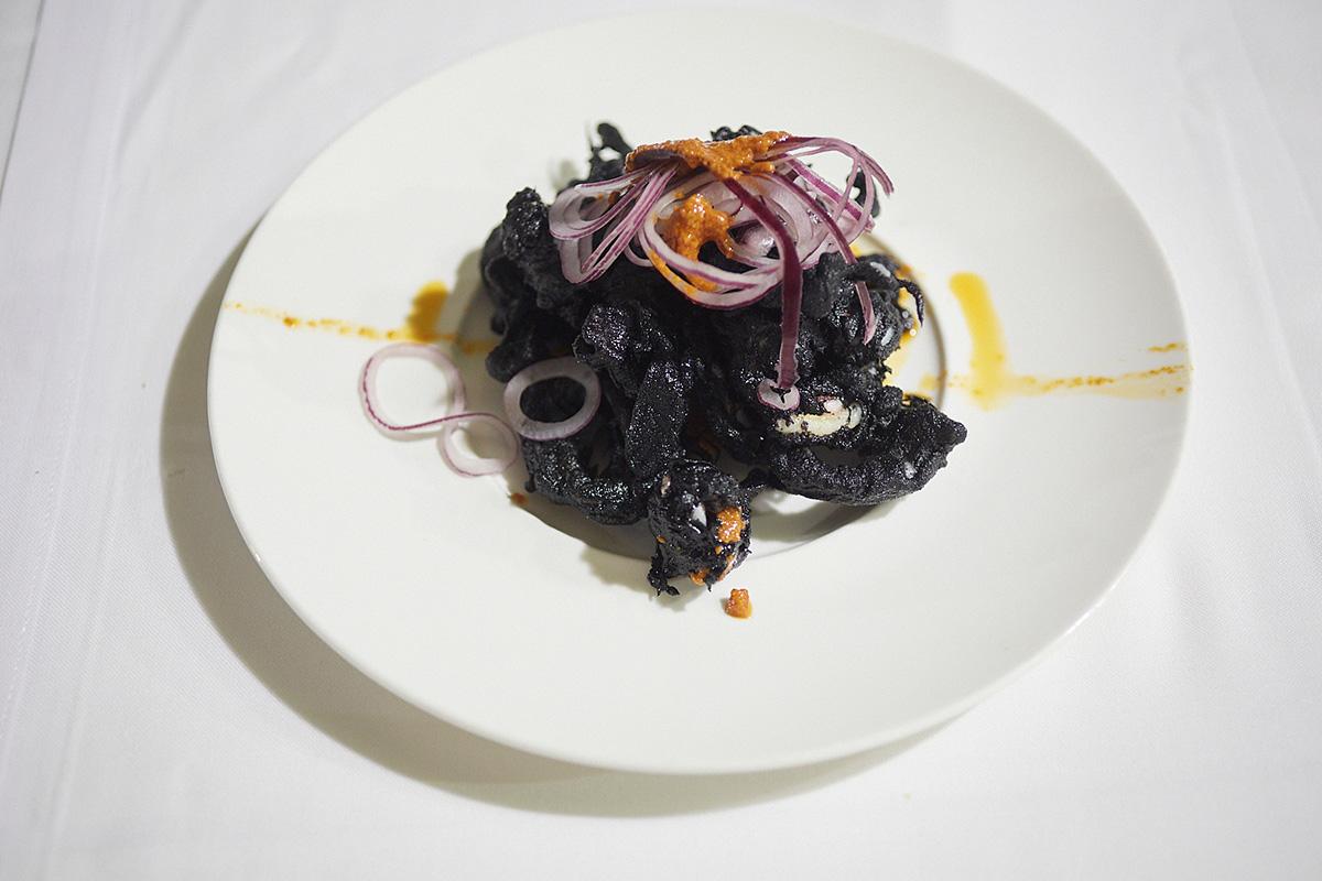 """Calamares de """"la platjeta"""" en tempura negra, cebolla laminada y aceite de romesco."""