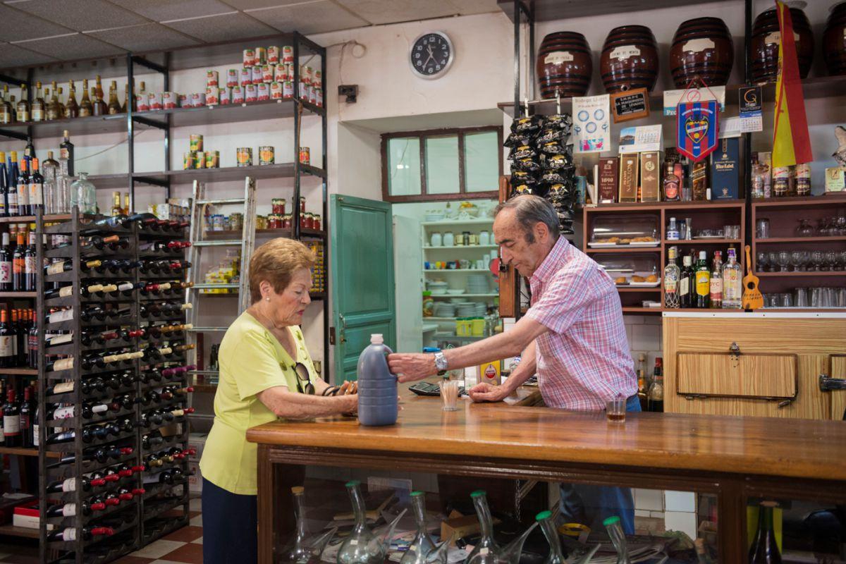 El propietario de la 'Bodega Lloret' en La Unión, Murcia, vendiendo botellas a granel a una vecina.