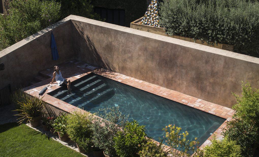 La piscina, resguardada de miradas, en la masía