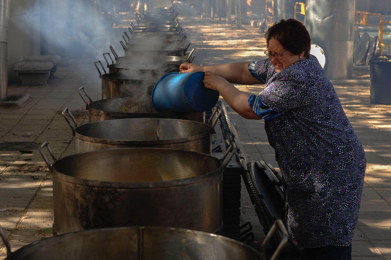 La cocinera va vertiendo en las ollas del cocido los ingredientes.