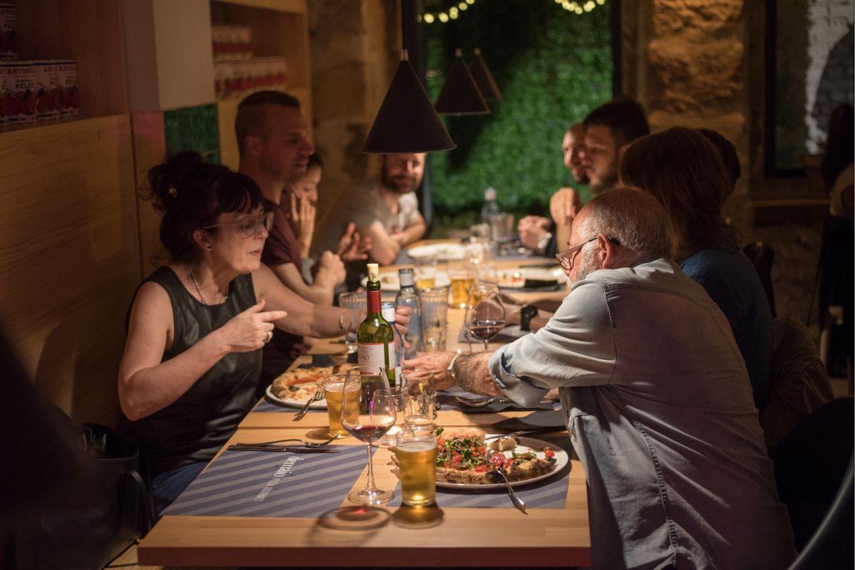 Compartiendo triángulos de 'pizza' en el comedor y tan a gusto como en casa. Foto: Demaio Pizza.