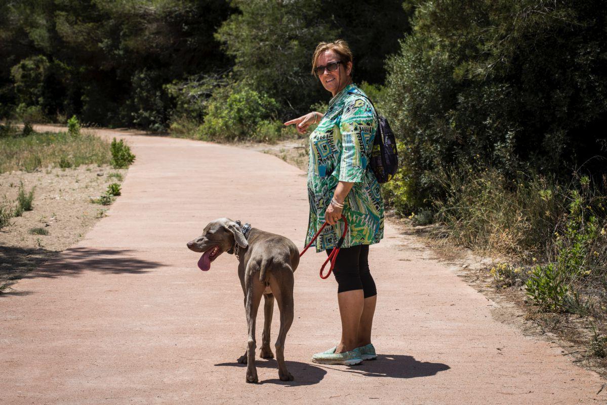 Una mujer pasea junto a su perro por la Dehesa de El Saler (Parque Natural de La Albufera, Valencia).
