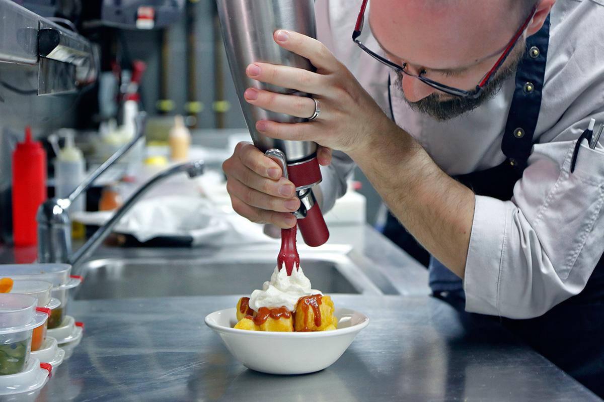 El chef Pedro Gallego preparando las patatas Massiel con espuma ligera de alioli.