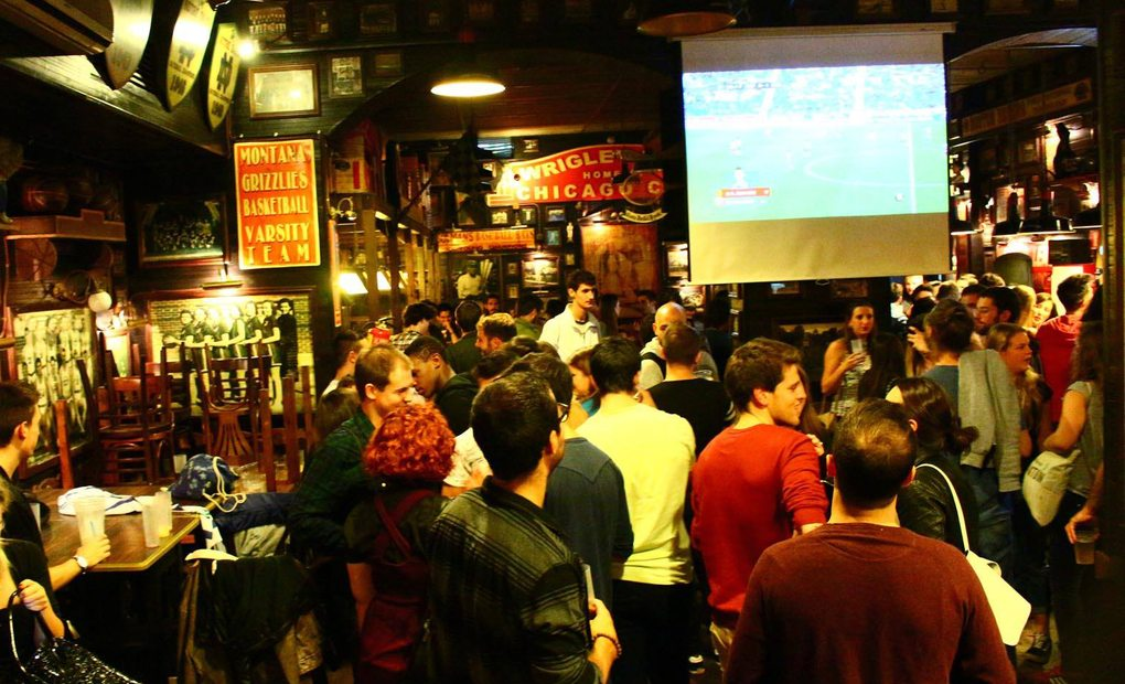 Bar lleno de gente con una pantalla y un partido proyectado.
