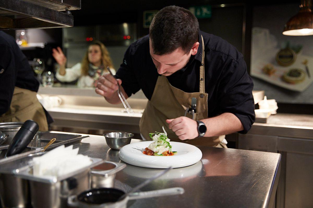 Uno de los cocineros del 'Caelis' ultima su plato de merluza.