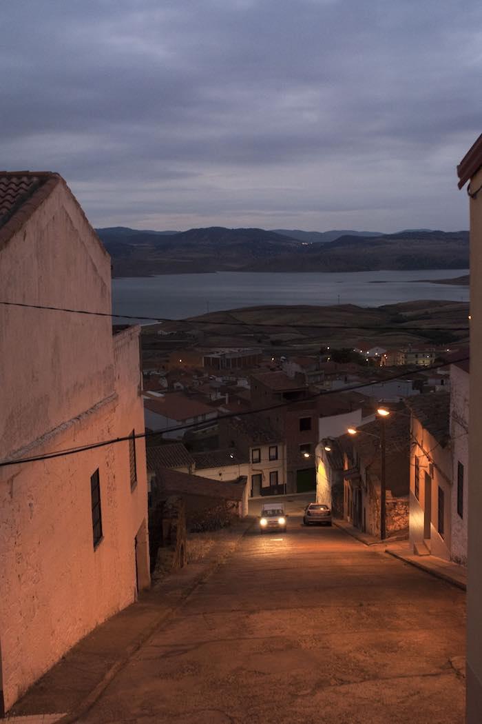 Calles desiertas al caer la noche en Peñalsordo, con el pantano al fondo.