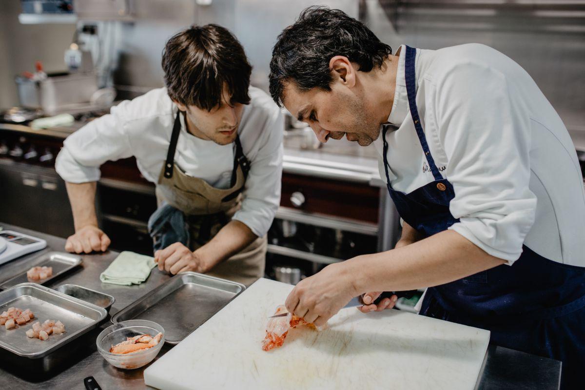El chef Javier Olleros quita la piel a un bogavante ante la mirada de un miembro del equipo de cocina del restaurante 'Culler de Pau', O Grove, Pontevedra.