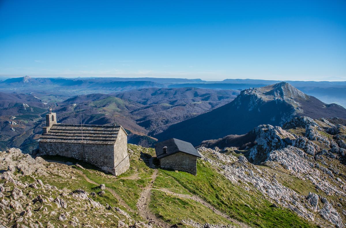 Vistas de la ermita del Santo Cristo y del refugio desde la cima del Aizkorri. Foto: Shutterstock.