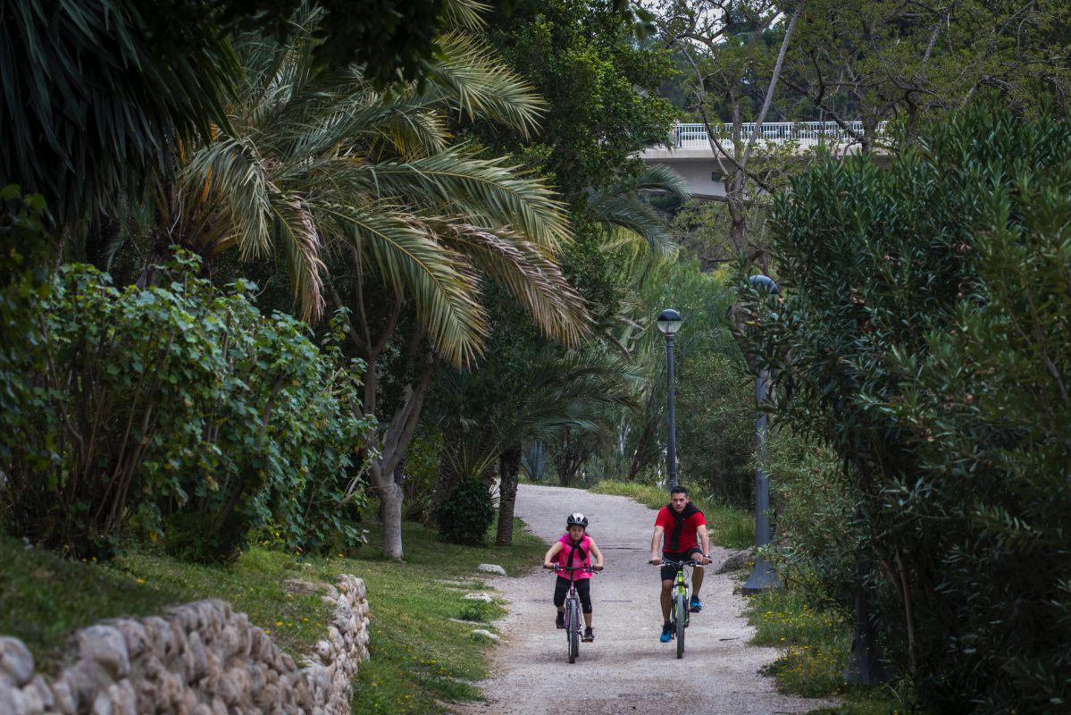 Un padre y una hija pasean en bici por la ladera del río Vinapoló, en Elche (Alicante).