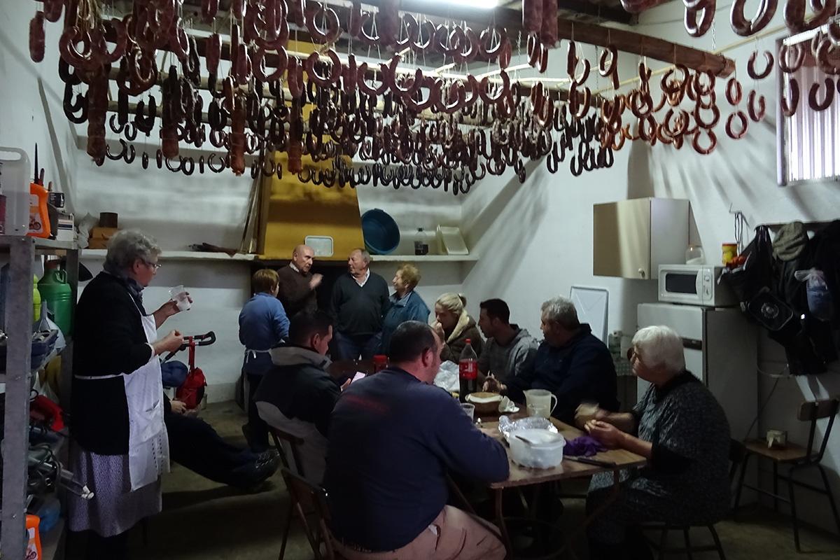 La familia durante el momento de descansar y tomar energías comiendo las clásicas migas, durante la matanza del cerdo ibérico, en la comarca de Los Barros (Badajoz).