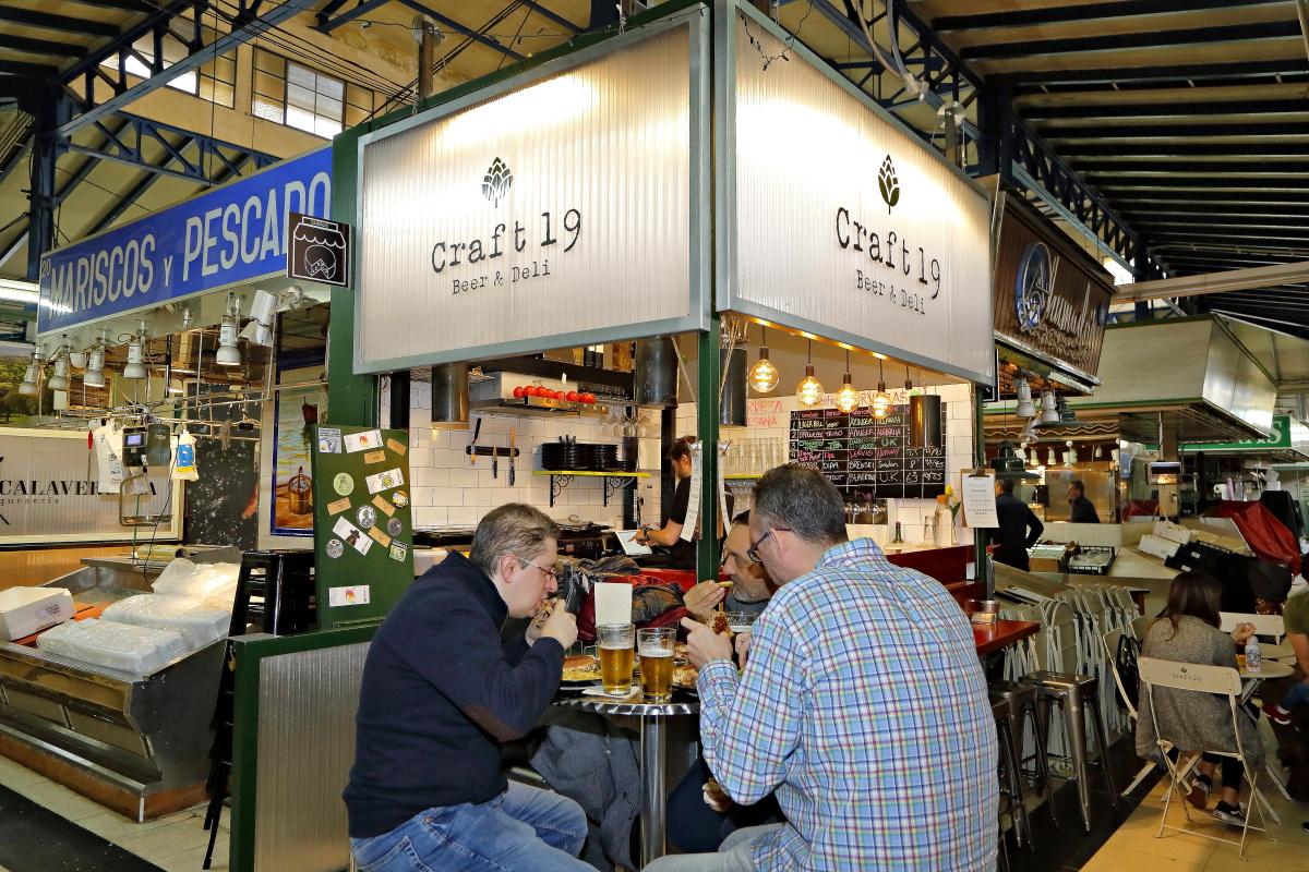 Unos clientes se comen un sándwich en las mesas de 'Craft 19' en el Mercado de Vallehermoso.