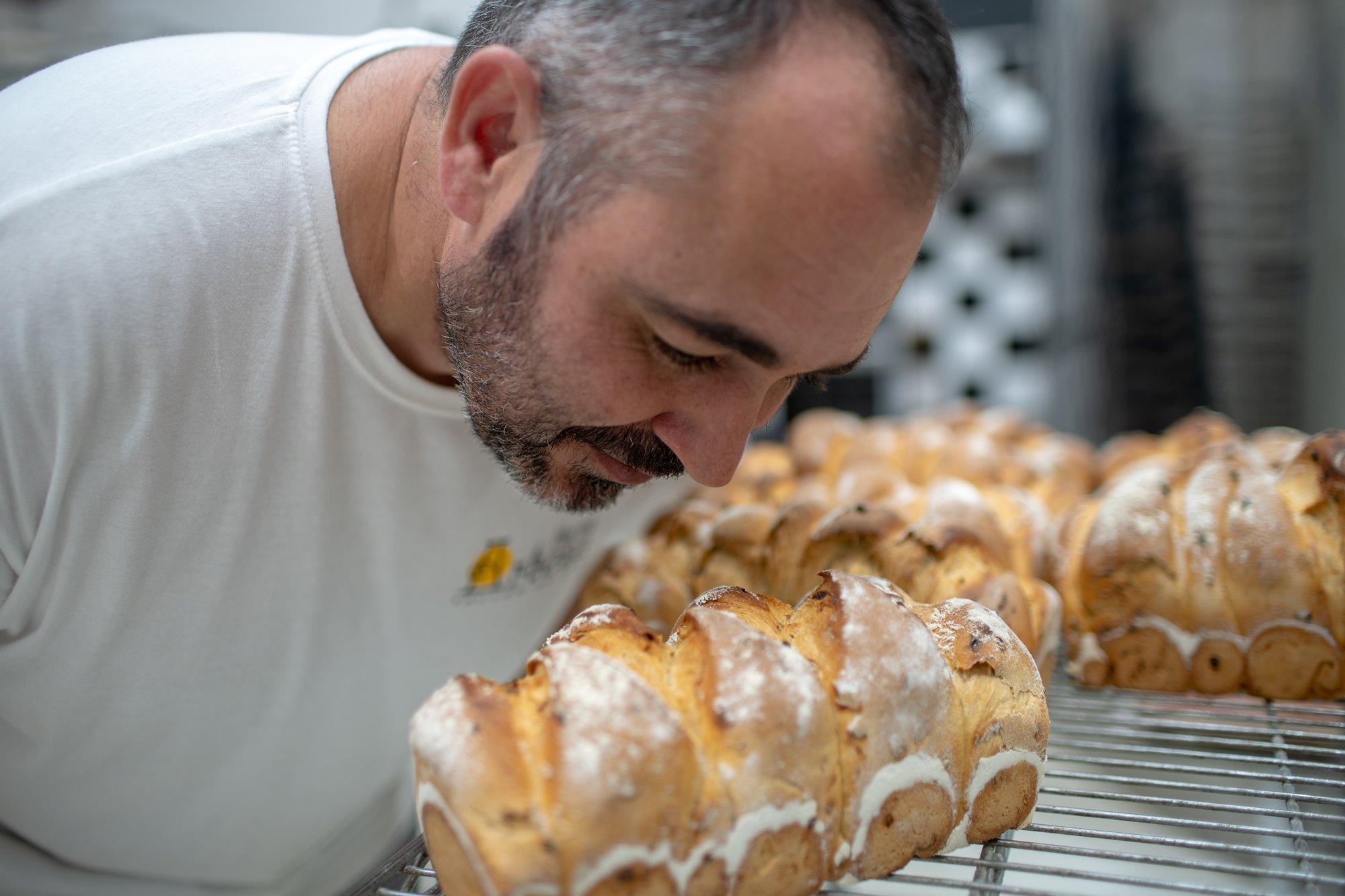 Paco huele el pan recién hecho de una de las dos remesas que se elaboran cada día.