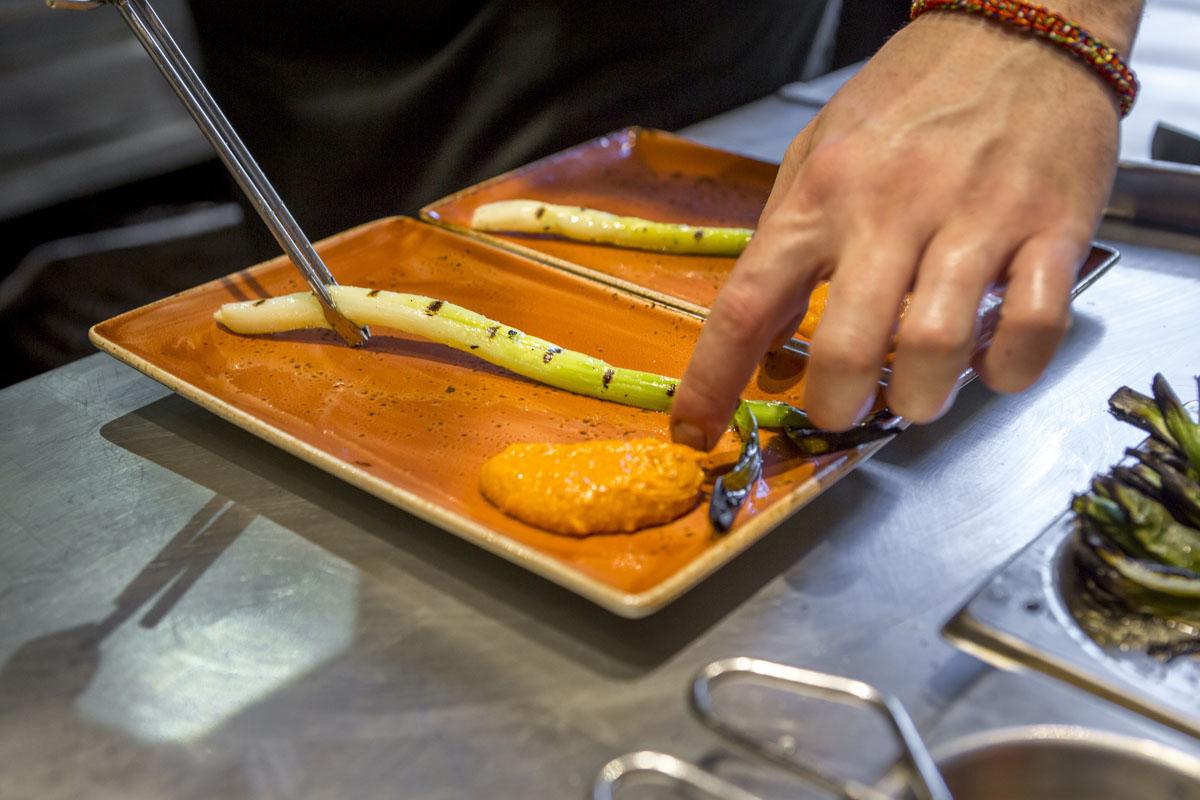 Un calçot con salsa romesco listo para degustar.