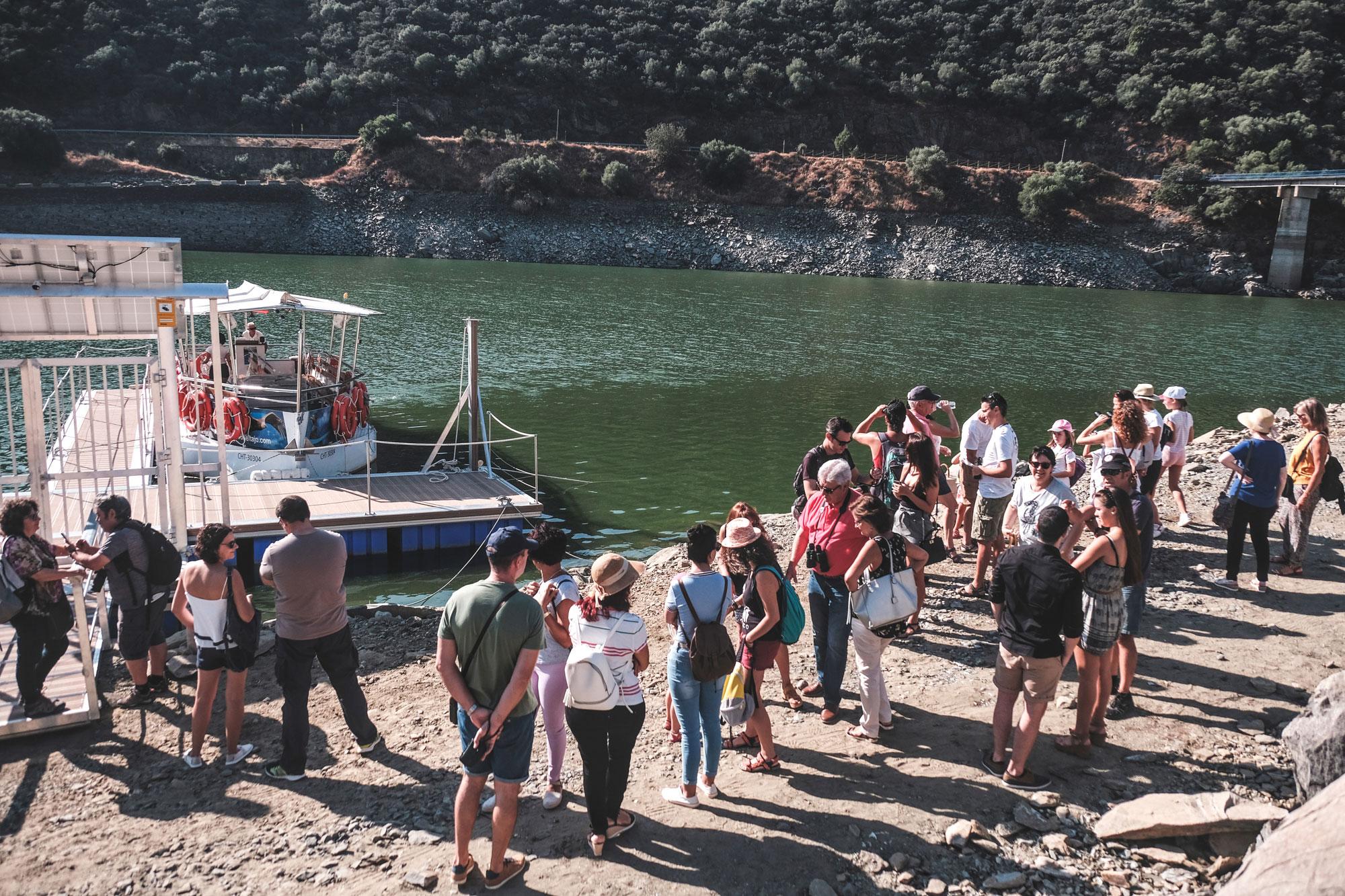 La gente espera en el embarcadero a que la tripulación termine de preparar el barco.