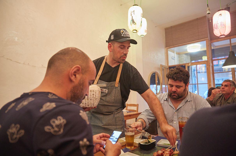 El chef Aitor Olabegoya se acerca a las mesas de los comensales a servir los platos y a charlar con ellos en su restaurante pop up en Poble Sec (Barcelona).