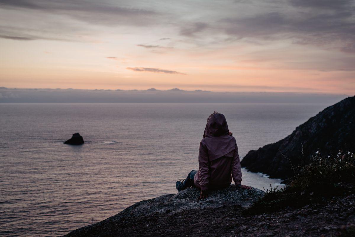 Una chica mirando el atardecer en O Camiño dos Faros (Costa da Morte, A Coruña).