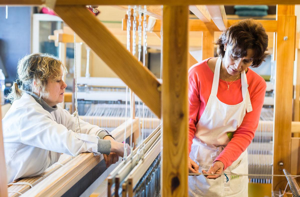 Dos tejedoras trabajan en el taller integrado en el Monasterio