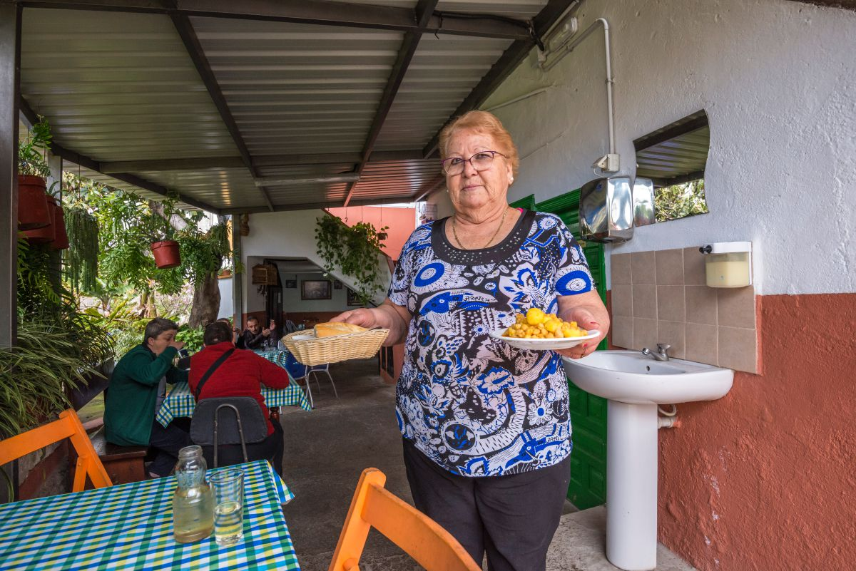 Una de las antiguas propietarias del guachinche Las Galanas, en Tenerife, sirve en una mesa del patio, un plato de garbanzas junto al vino.
