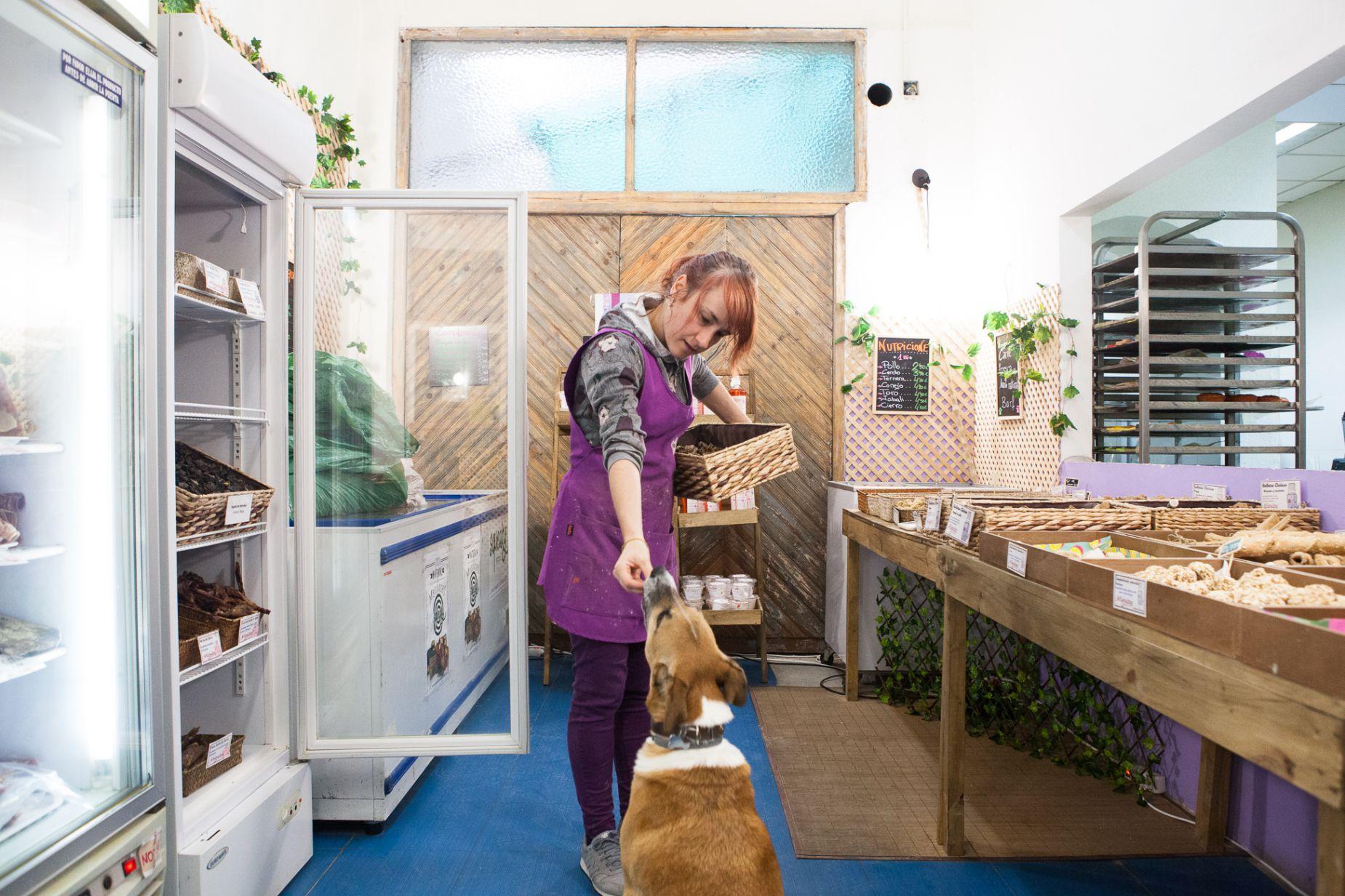 Tienda obrador 'Miguitas' (Madrid): dependienta dándole una galleta a un perro