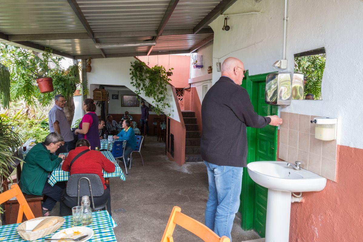 Las mesas en el patio del guachinche Las Galanas rodeados de macetas.