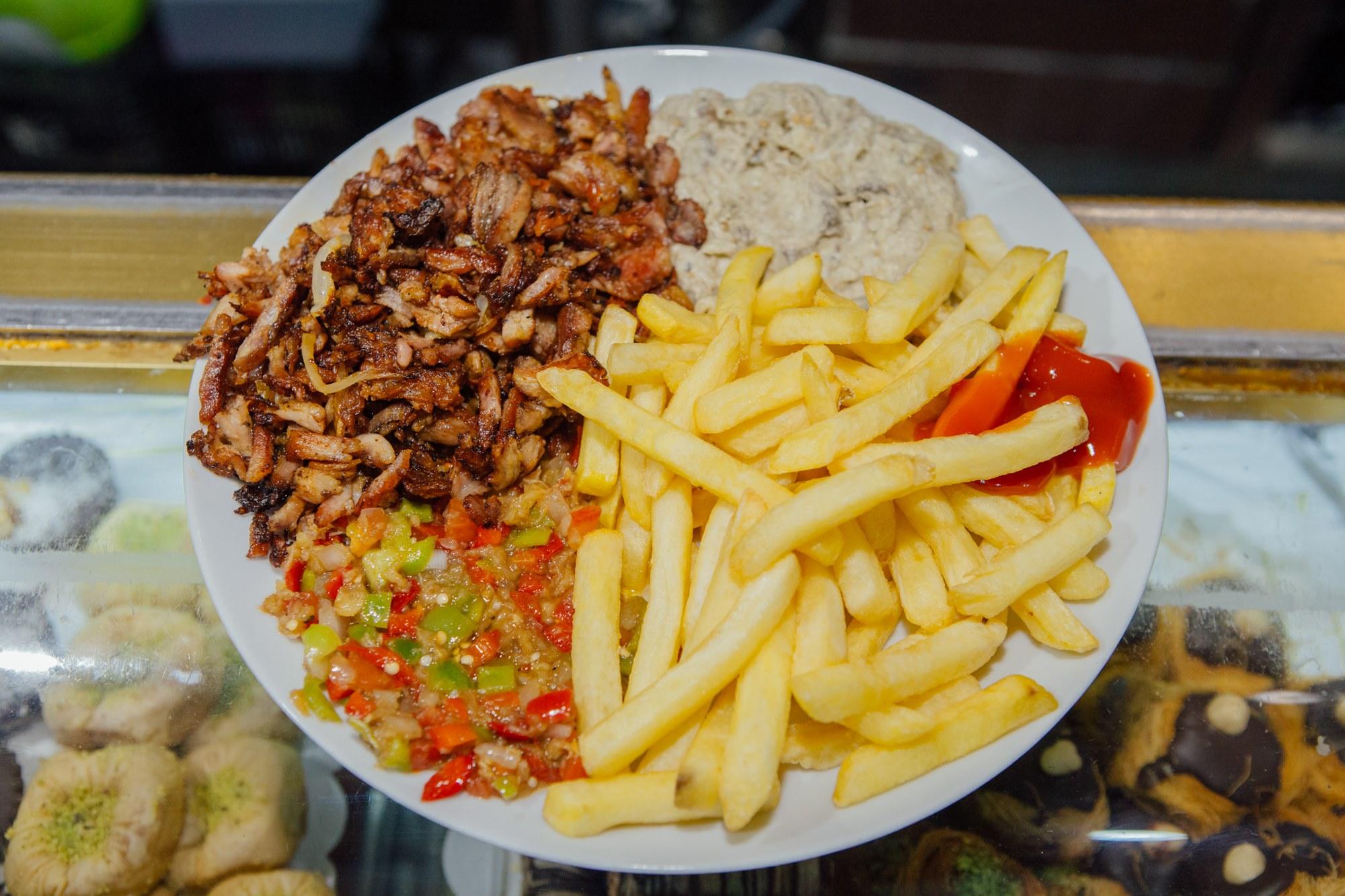 Plato de carne, ensalada de pimientos, baba ganoush (crema de berenjena) y patatas fritas.
