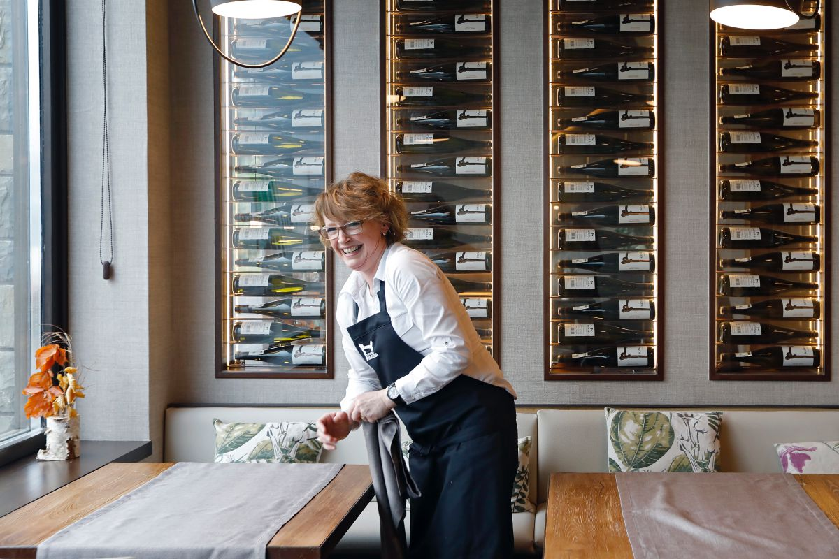 En el restaurante y'Bodega Katxiña', en Orio, Guipúzcoa, una camarera prepara las mesas, con las botellas del vino de allí mismo detrás.