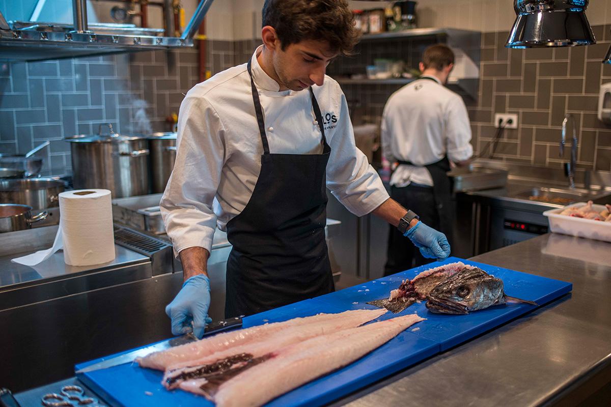 El chef Infantes preparando el pescado en la cocina.