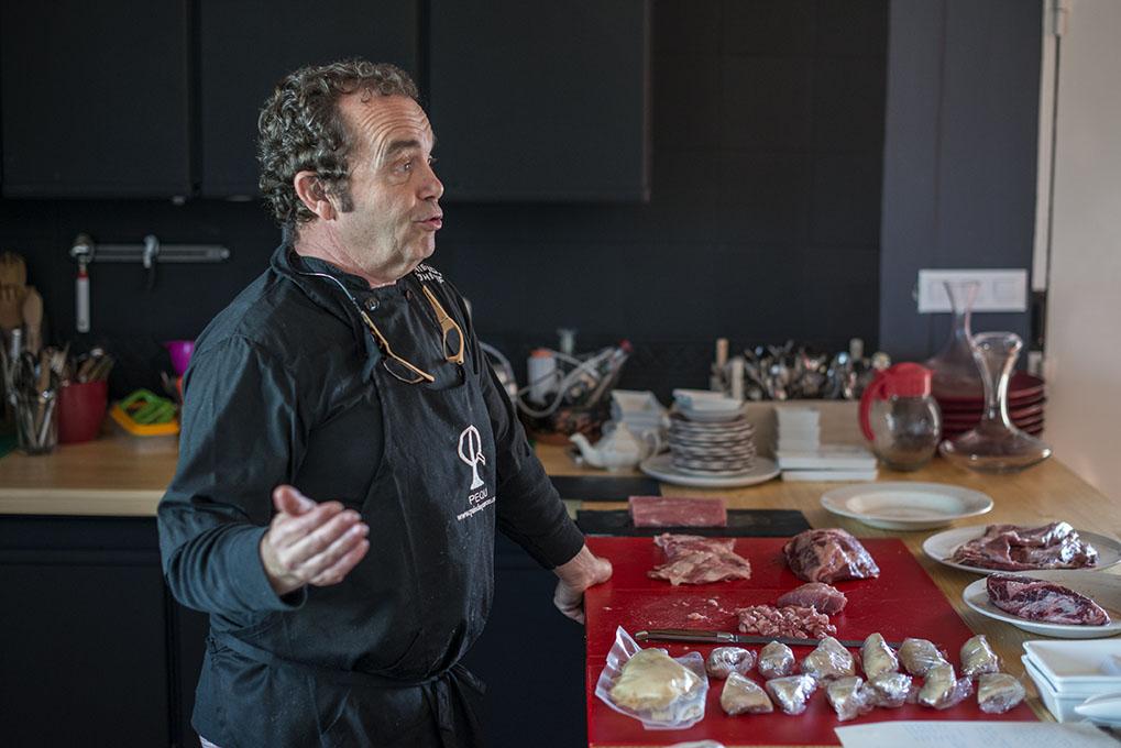 Carlos Tristancho a punto de cocinar el cochinillo, junto a otras carnes.