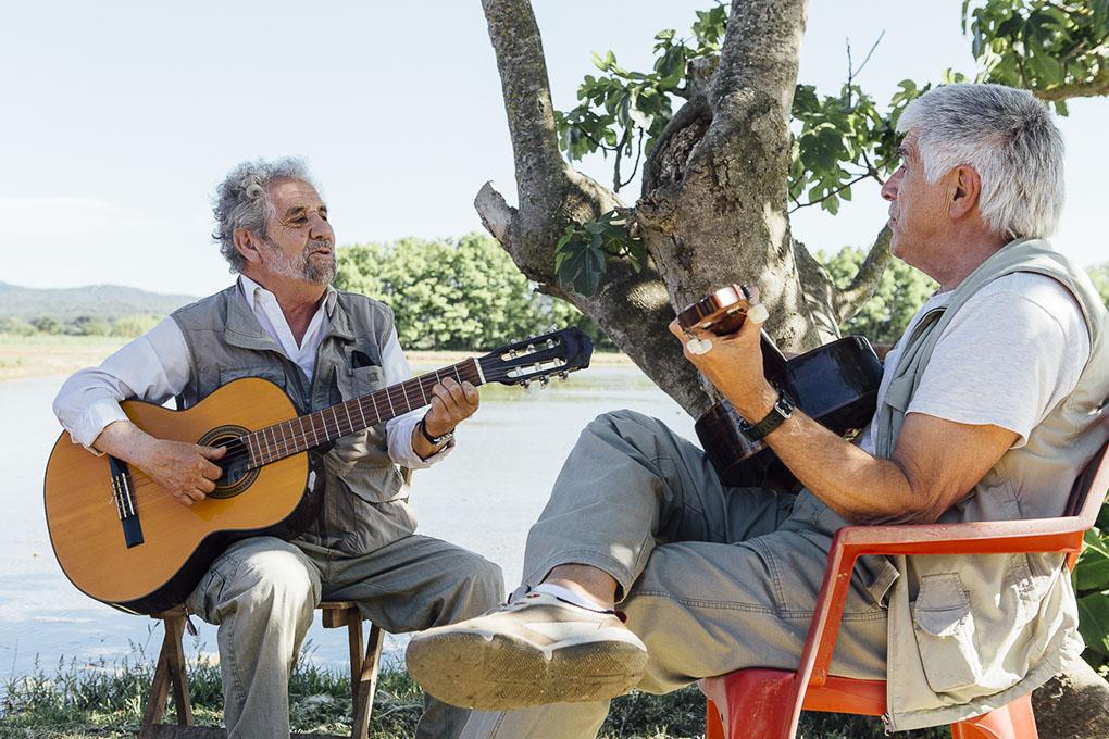Ricard y Josep Lluis amenizan la sobremesa con sus habaneras a la sombra de una higuera.